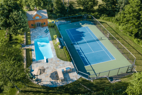 tennis court blacktop regulation timber frame pool house gunnite pool bluestone patio outdoor kitchen katonah westchester aerial