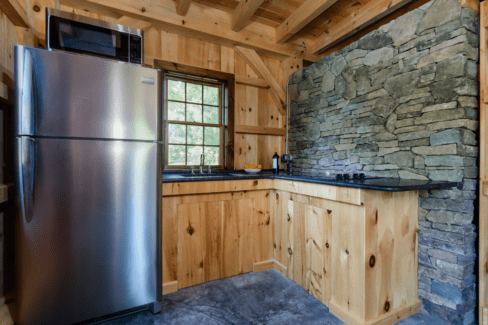 post beam style timber frame pool house northern white pine ashlar stone barn door hardware cement slab floor radiant heat kitchen honed granite counter katonah westchester