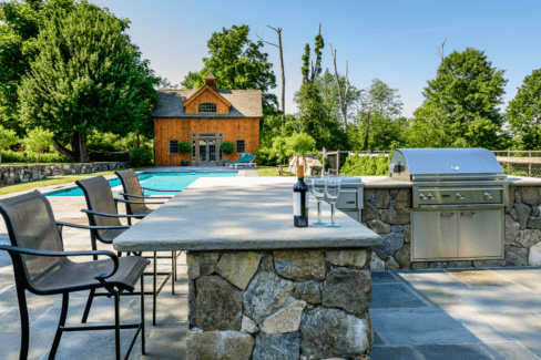 outdoor kitchen bluestone patio faced fieldstone counter Lynx appliances pool house spa katonah westchester
