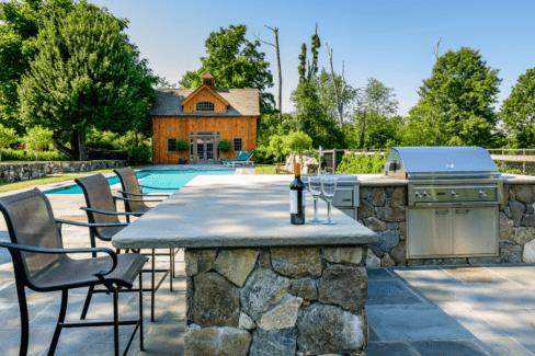 outdoor kitchen bluestone patio faced fieldstone counter Lynx appliances pool house spa katonah westchester